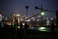 "CHINA. Chongqing. May 2007. Migrant workers (mingong) at night on the construction of the ""Cite des sciences et Techniques"" by"