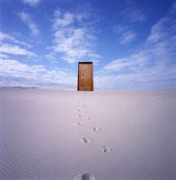 砂漠の足跡と青空にドア