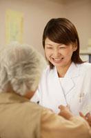 日本人の老人女性患者に説明をする女性薬剤師
