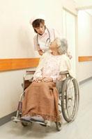 車椅子の日本人老人女性患者を押す日本人看護婦