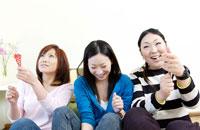 パーティーでクラッカーを鳴らす3人の笑顔の日本人女性