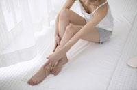 組んだ脚を手で押さえる日本人女性