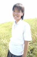 野原に立つ日本人女性中学生