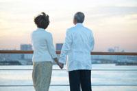 甲板に立ち手を繋ぐ中高年夫婦の後姿