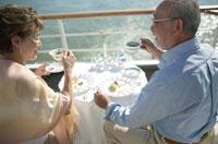 クルーズ船で食事をする中高年夫婦