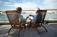 甲板で椅子に座り飲み物を飲む中高年夫婦の後ろ姿