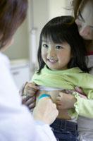 お腹に聴診器をあてられる女の子の患者