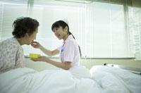 シニア女性患者に食事をあげる女性看護師 02266011529B| 写真素材・ストックフォト・画像・イラスト素材|アマナイメージズ