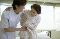 シニア女性患者を支える男性看護師