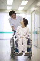 シニア女性患者の車椅子を押す男性看護師