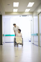 シニア女性患者の車椅子を押す女性看護師