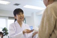 薬を渡す女性看護師とシニア男性患者