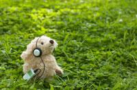 ヘッドフォンで音楽を聴く犬のヌイグルミ