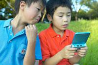 ベンチに座ってゲームをする少年達