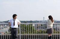 屋上の柵にもたれる高校生男女