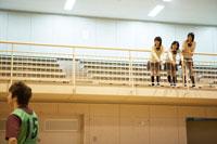 体育館で応援をする女子高校生