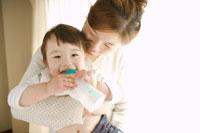 哺乳瓶を吸う赤ちゃんと母親