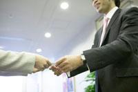 名刺を渡す男性と受付女性 02266014501| 写真素材・ストックフォト・画像・イラスト素材|アマナイメージズ