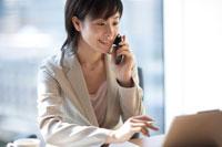 デスクで携帯電話をかける女性