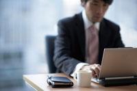 パソコンに向う男性とビジネス手帳