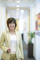 廊下に立つ笑顔の女性上司 02266014594B| 写真素材・ストックフォト・画像・イラスト素材|アマナイメージズ