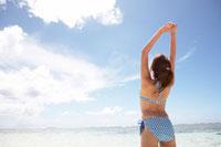 背伸びをする女性と青空と海
