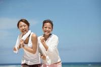 砂浜でジョギングする女性2人