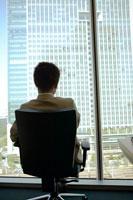 椅子に座る男性の後姿と高層ビル