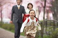 歩道を歩く両親と走る女の子
