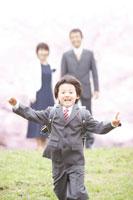 土手に立つ両親と走る男の子と桜