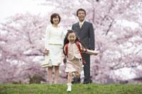 土手に立つ両親と走る女の子と桜