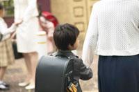 母親と手をつなぐ小学生の男の子