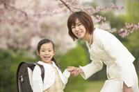 桜の下に立つ女の子と母親