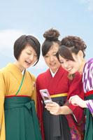 携帯を見る袴を着た女性