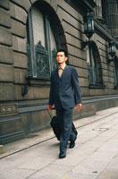 スーツケースを引いて歩く日本人ビジネスマン