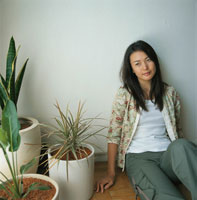 壁にもたれて座る日本人女性と観葉植物 02274000106  写真素材・ストックフォト・画像・イラスト素材 アマナイメージズ