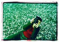 桜の花びらの上でカメラを構える外国人女性