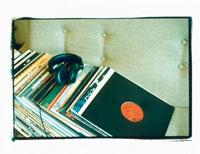 部屋のソファに置かれた複数のレコードとヘッドフォン