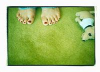 女性の足とぬいぐるみ