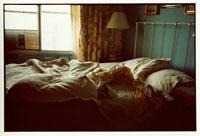 乱れたシーツと枕のベッドとランプ