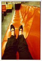 ベンチ(オレンジ色)に座る女性の脚