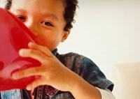 風船を膨らます男の子 02275000143| 写真素材・ストックフォト・画像・イラスト素材|アマナイメージズ