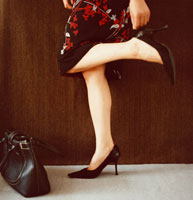 ハイヒールを履く女性の足元に置かれたバッグ