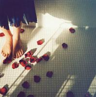 タイルに散らばるバラの花びらとはだしの足
