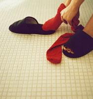 靴下(赤)を履く足とスリッパ