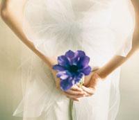 後ろ手に花を持つ女性の手