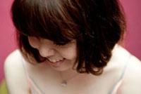 うつむいて笑うボブヘアの20代女性