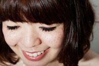 うつむいて笑うそばかすのあるボブヘアの20代女性