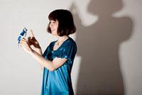 青い鳥の人形を手につけたワンピースを着た20代女性