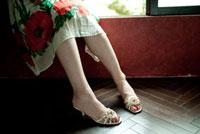 窓辺に座るサンダルを履いた女性の足元